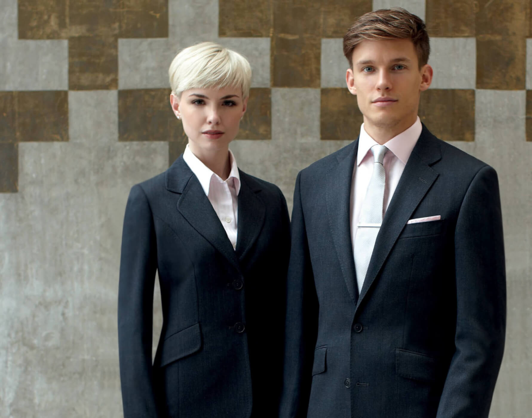 corporate clothing: man and woman in charcoal suits and pale pink shirts